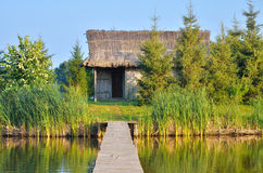 Thatched cottage on the lake Stock Photography