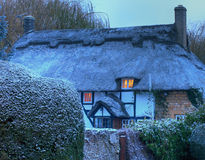 Thatched cottage with snow. Black and white, timber-framed thatched cottage in winter, Mickleton near Chipping Campden, Gloucestershire, England Royalty Free Stock Photography