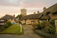 Thatched hamlet. Idyllic hamlet of thatched cottages at sunset with church in background Royalty Free Stock Image