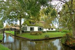 Thatched house on waterside. Scenic picture of a white painted thatched house in the countryside situated next to the water in the scenic touristic village stock photography