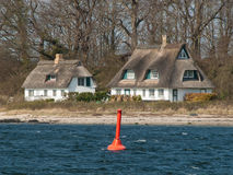 Thatched houses at the beach of the Schlei Stock Photos