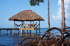 Thatched hut with hammock over the sea Stock Photo