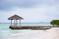 Thatched pavilion on the beach in maldives Royalty Free Stock Photo