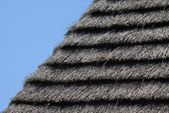 Thatched Roof. Primitive Layered Thatched Roof Against Blue Sky royalty free stock photo