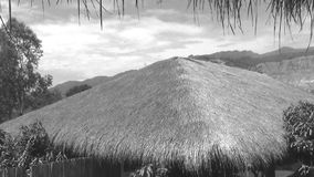 Thatched roof on a background of mountains and  sky. Black and white shooting stock footage