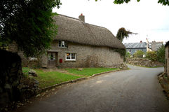 Thatched roof on cottage.. Thatched roof on a cottage in rural wester England - Cornwall.  Leading lines along country road Royalty Free Stock Photo