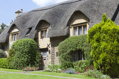 Thatched roof cottage with flowering garden in an english countryside . Stock Photo