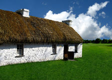 Thatched Roof Home in Grassy Field. A white home made of field stone with a thatched roof sits in a grassy meadow royalty free stock photos