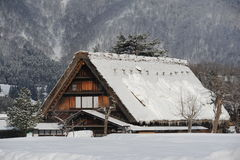 Thatched roof house covered in snow in winter Royalty Free Stock Photos