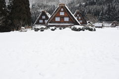 Thatched roof houses covered in snow in winter Stock Images
