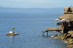 Thatched roof hut with floating deck. Beach palapa  with floating deck on the Mexican Pacific Ocean, near Puerto Vallarta Royalty Free Stock Images