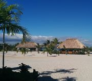 Thatched-roof huts on tropical island. With palm trees, clouds, and shadows Stock Photos