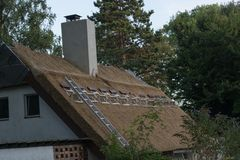 Thatched roof is newly covered. Professional execution of a repairs to a thatched roof stock photos