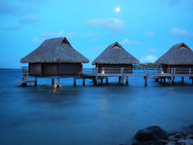 Thatched roof overwater bungalows at blue hour. Three thatched roof overwater bungalows in a luxuous honeymoon resort in the water of the lagoon of the tropical royalty free stock images