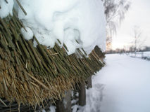 Thatched roof under the snow. A layer of snow on the thatched roof. and behind a small fence Stock Photos