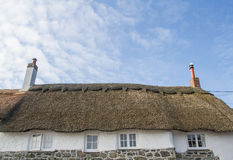Thatched Stone Cottage. Looking up to the roof of a traditional thatched stone cottage with brick chimney pots under a blue sky Stock Photos