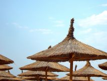 Thatched straw umbrellas Stock Photos