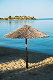 Thatched sunshade on a beach in front of old Roman fortress, Sithonia Royalty Free Stock Photo