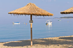 Thatched sunshade on a beach reserved for you in Sithonia Stock Images