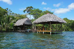 Thatched tropical hut and boathouse over the sea Stock Photography