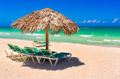 Thatched umbrellas and beach beds on a cuban beach Stock Photo