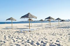 Thatched umbrellas and beach chairs on the beach Royalty Free Stock Photos