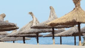 Thatched Umbrellas on Beach. With the wavering blue sea in the background stock footage