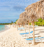 Thatched umbrellas at a tropical beach in Cuba. Umbrellas and out of focus people at a beach in Cayo Coco (Coco key), a natural tourist destination in Cuba Royalty Free Stock Image