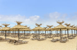 Thatched umbrellas and wooden lounge chairs on the beach. Stock Image