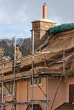 Thatcher at work. EXFORD, ENGLAND - OCTOBER 12, 2014: Thatcher at work in an Exmoor village recovering a thatched cottage roof royalty free stock photos
