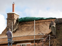 Thatchers at work on Exmoor UK. EXFORD, ENGLAND - OCTOBER 12, 2014: Thatchers at work in an Exmoor village recovering a thatched cottage roof Stock Photo