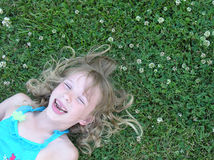 Thats funny. A young girl laying down on the grass laughing in response to a funny joke Royalty Free Stock Image