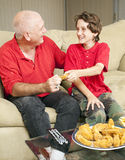 Thats My Chicken Wing. Little boy and his father watching football and fighting over a fried chicken wing Royalty Free Stock Photography