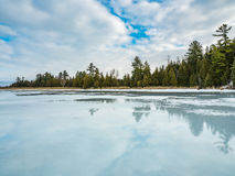 Thaw Cedar Forest Beside Frozen Marsh. Winter Thaw Cedar Forest Beside Frozen Marsh water covering the ice from an early winter thaw Royalty Free Stock Images
