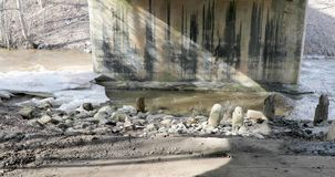 Thaw and the movement of the river under the bridge next to the broad leaves of ice.  stock footage