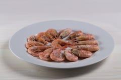 Thawed kokade räkaräkor som humret är på en vit platta Rå liten rosa räka i skal med huvudet och svansen arkivfoto