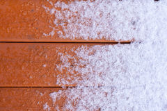 Thawing fresh snow on wooden deck planks. Winter nature background pattern abstract contrast of fresh snow melting on wet wooden deck plank surface stock image