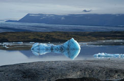Thawing River Scenery. Scenery image of thawing icebergs floating in the river and blue hazed mountains off in the distance Stock Photo