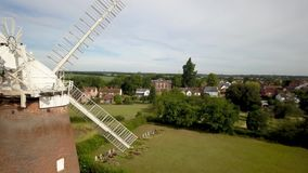 Thaxted village and windmill, Essex, England. 4K aerial drone video footage reversing to reveal the landmark windmill overlooking the rural Essex village of stock video