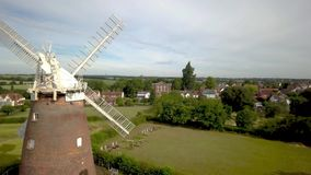 Thaxted Village and Windmill, Essex, England. 4K aerial video footage passing forward through the blades of the old windmill overlooking the rural English stock video footage