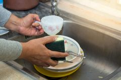 The​ Hand cleaning of female or housewife woman washing dishes with a yellow sponge in kitchen sink. Hand cleaning of female or housewife woman washing stock photos