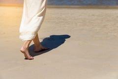 TheLage hoek achter vrouw het lopen blootvoets op strand royalty-vrije stock fotografie