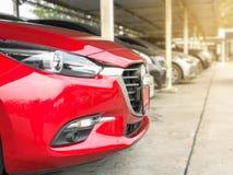 Thenieuwe rode auto in geparkeerd met vele auto's op parkeerterrein stock fotografie