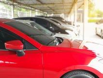 Thenieuwe rode auto in geparkeerd met vele auto's op parkeerterrein stock afbeeldingen