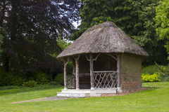 The 19th Century Thatched Summer House Surrounded By Beautiful Flower Beds And Gravel Paths In The Walled Garden At West Dean Stock Photography