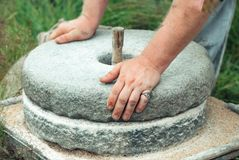 Free The Ancient Stone Hand Grain Mill. Men`s Hands Rotate A Stone Millstone Stock Photos - 113490653