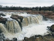 Free The Big Sioux River Flows Over Rocks In Sioux Falls South Dakota With Views Of Wildlife, Ruins, Park Paths, Train Track Bridge, Tr Royalty Free Stock Photos - 113901488