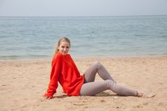 Free The Blonde In The Red Walks Along The Beach Of The Sea Coast Royalty Free Stock Photos - 114969778