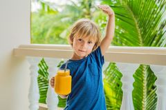 The Boy Holds Mason Jar Of Mango Smoothies In His Hand And Shows Stock Image