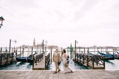 Free The Bride And Groom Are Walking Along The Gondola Pier, Holding Hand In Venice, Near Piazza San Marco, Overlooking San Stock Photos - 182763533